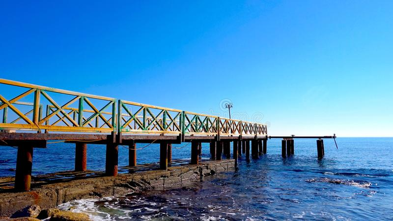 Old Pier lurking over the Sea stock photography