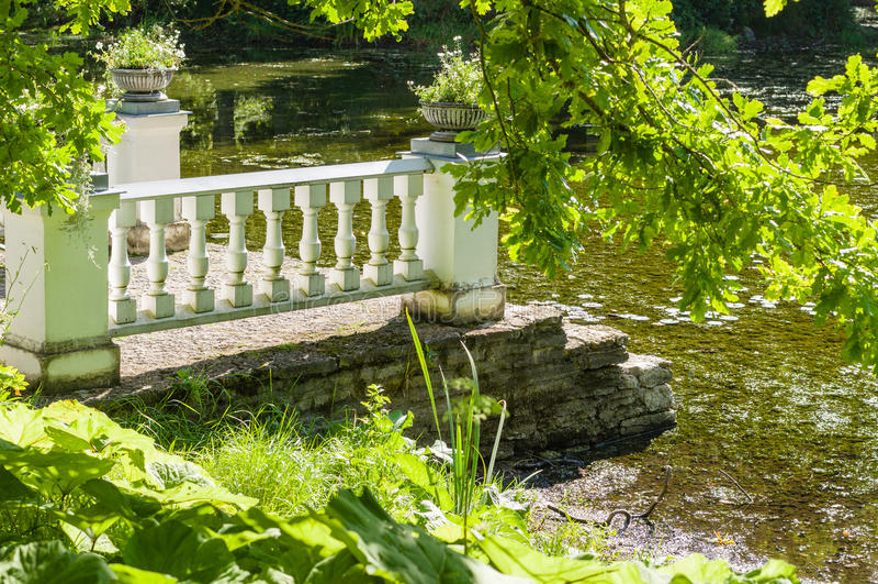 Old pier and pond through greenery. Of Sagadi park, Estonia stock photos