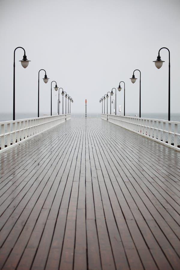 Old pier in rain on Baltic sea Gdynia Poland. White old pier in rain on Baltic sea Orlowo Gdynia Poland royalty free stock photos