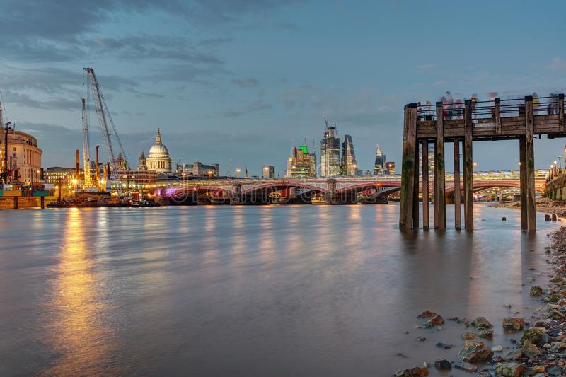 An old pier, the St Pauls cathedral, Blackfriars Bridge and the City of London. At dusk stock images