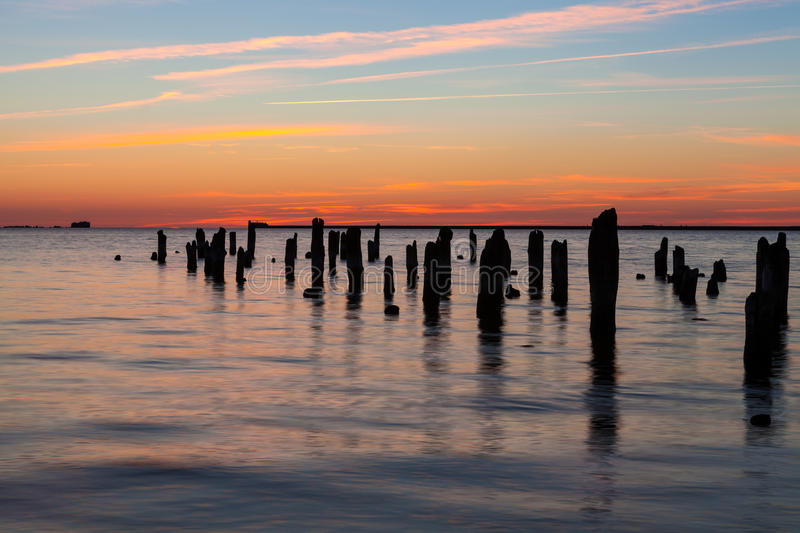 Old pier. Old wooden pier in harbor at sunset royalty free stock images