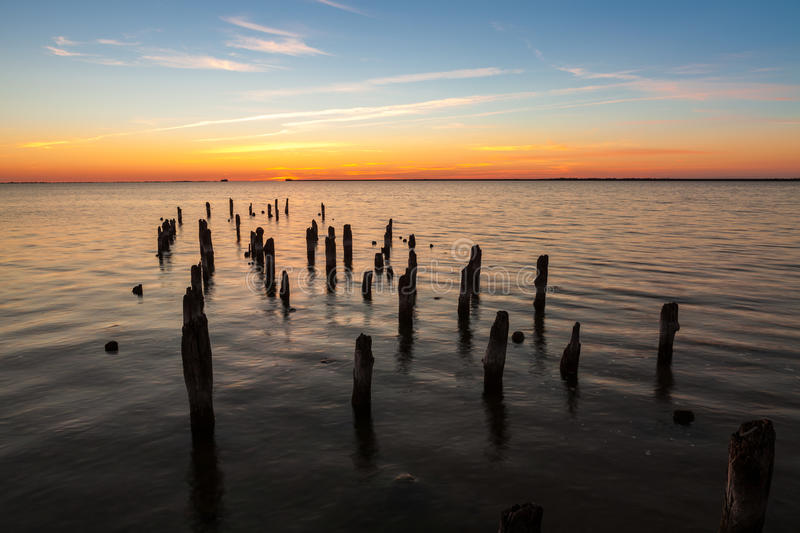Old pier. Old wooden pier in harbor at sunset royalty free stock photography
