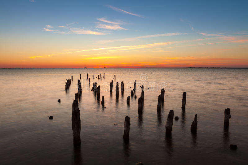 Old pier. Old wooden pier in harbor at sunset stock image