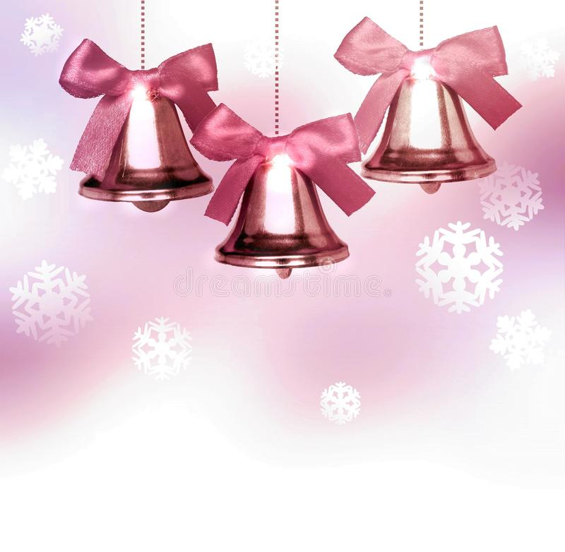 Old pink Christmas bells with snowflakes. Old pink Christmas bells with a bow. The back has a delicate pink background with lights and snowflakes. Easy winter stock photos