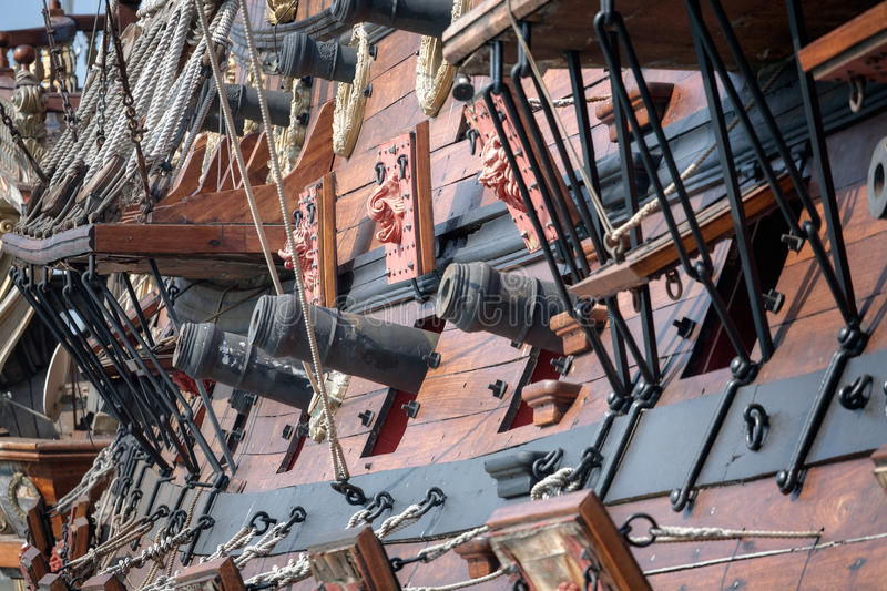 Old pirate ship cannons. Old pirate ship with cannons on dockyard - retro style toned photo royalty free stock images