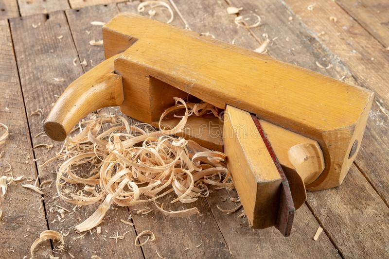 Old planer on a wooden carpentry table. DIY accessories in an old workshop. Dark background stock photos