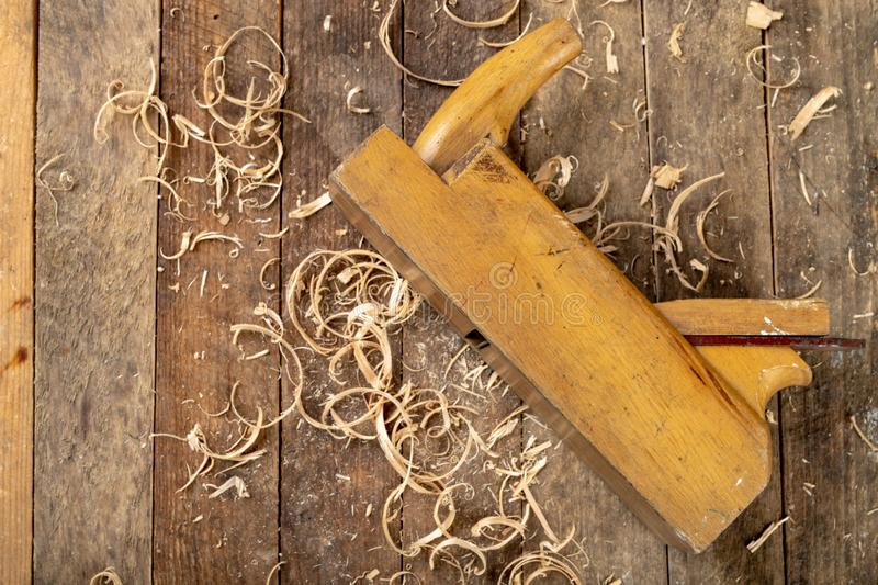 Old planer on a wooden carpentry table. DIY accessories in an old workshop. Dark background stock image