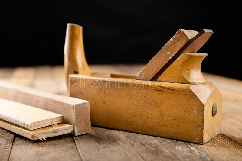 Old planer on a wooden carpentry table. DIY accessories in an old workshop. Dark background royalty free stock photos