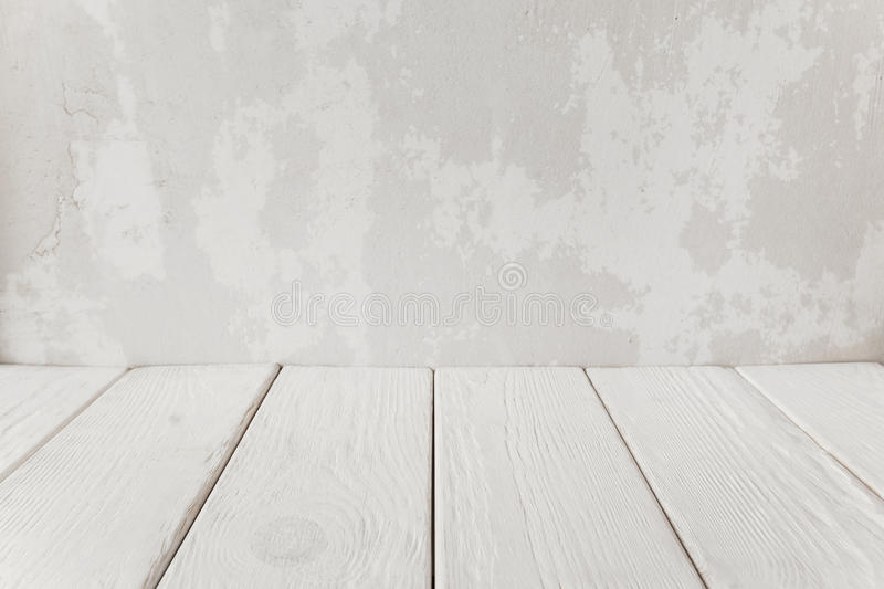 Old plaster wall with white wooden floor, close-up stock photo