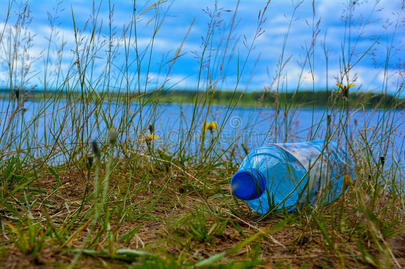 An old plastic bottle lies on the river bank in the grass. Eco concept Trash disaster from environmental pollution. The problem of stock photo