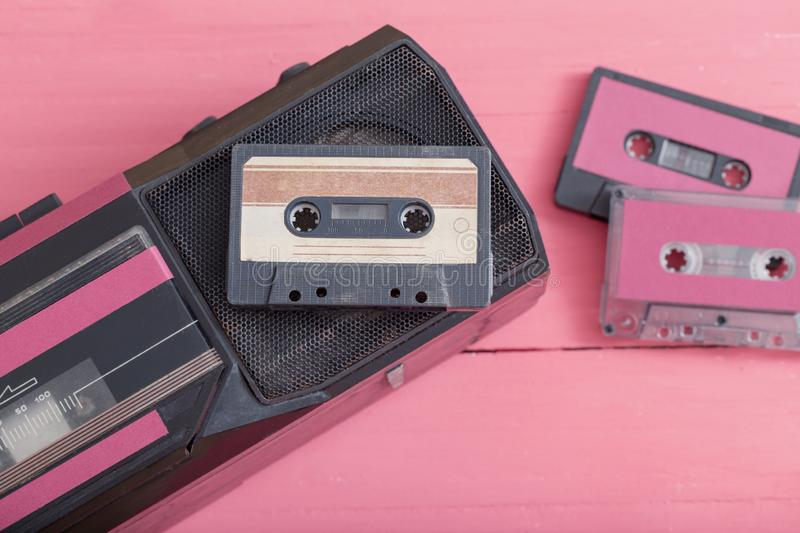 Old plastic cassette with tape recorder on wooden background. Retro music concept stock photo