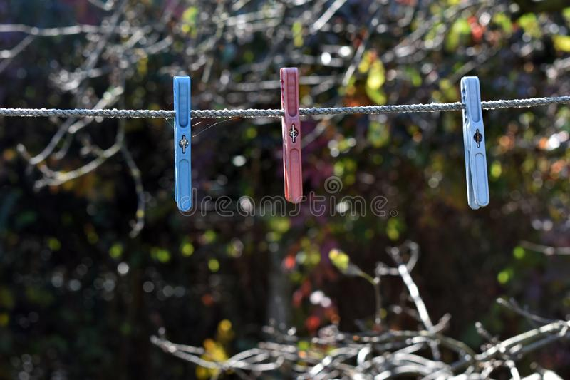 Old plastic clothespin hanging on a rope royalty free stock images