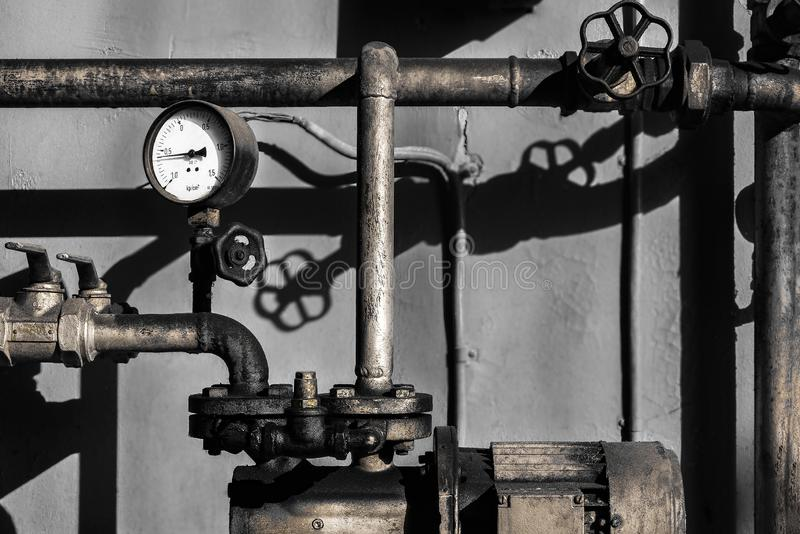 Old plumber pipes with a bar meter stock photo