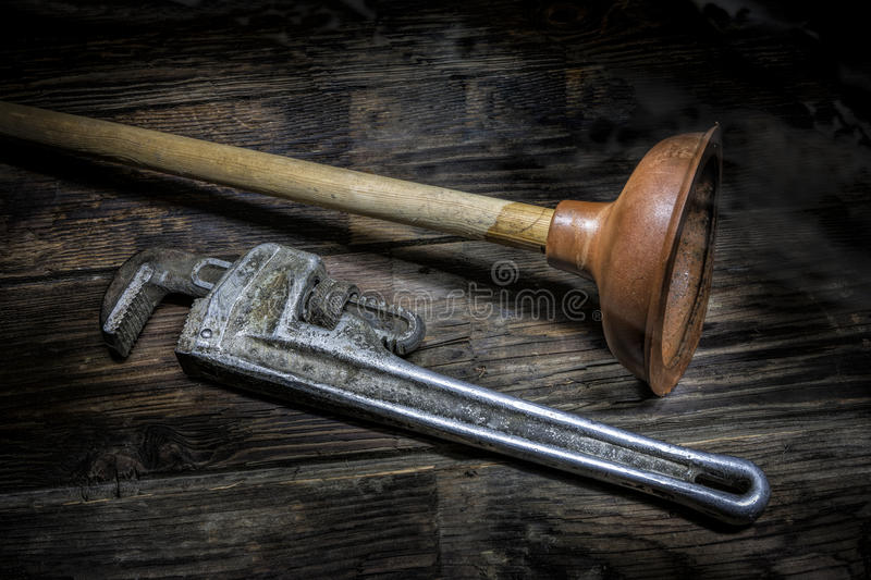 Old plunger and pipe wrench. A concept image of a pipe wrench and an old plunger royalty free stock image