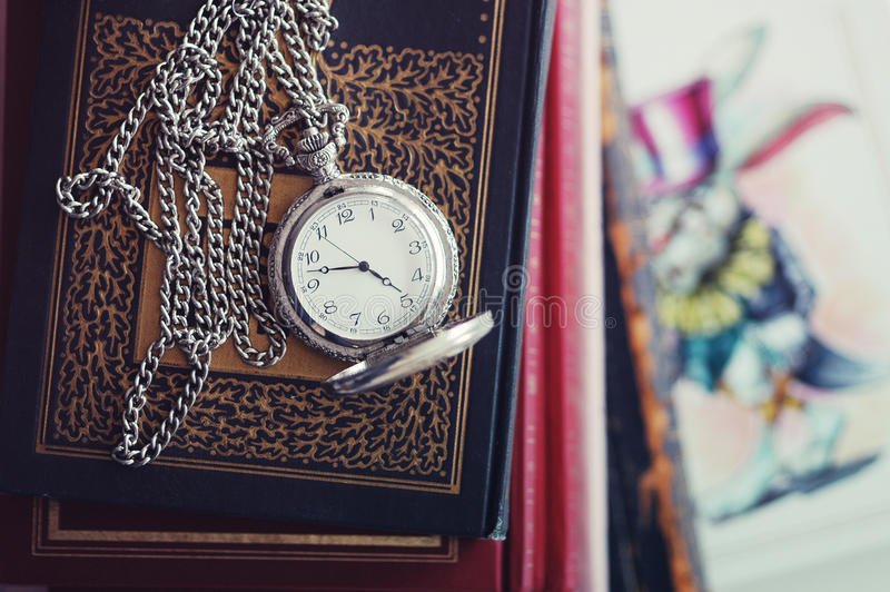 Old pocket-watch and books stock photography