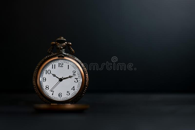 Old pocket watch on dark background. Watches, pockets, clocks, antiques, backgrounds, darks, olds, ageds, vintages, concepts, classics, retros, times, hours stock images