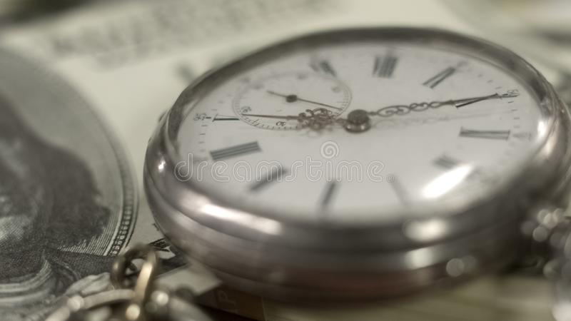 Old pocket watch on dollar bill, money working, time running out, world economy stock image