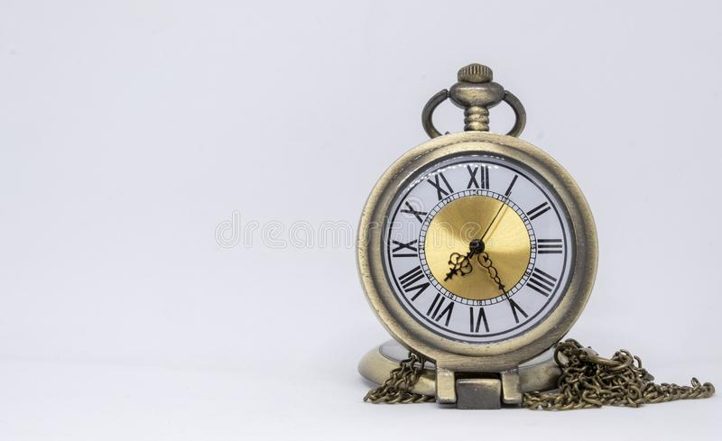 The old pocket watch is a necklace located on the white floor being separated. Isolated background chain antique time vintage beautiful clock retro object metal royalty free stock image