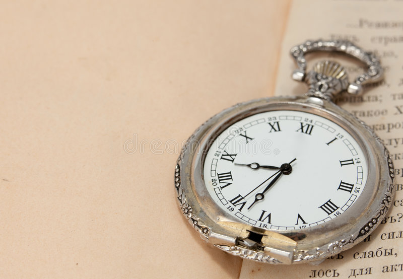 Old pocket watch over vintage book. copy space stock photography