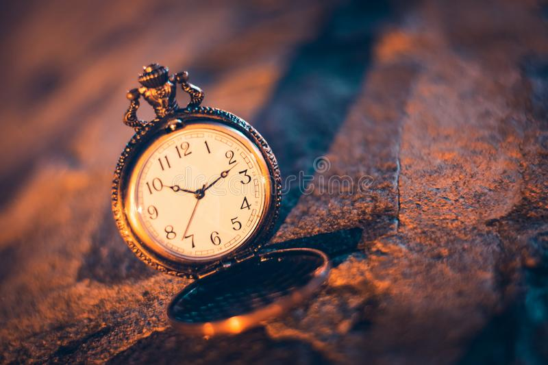 An old pocket watch photographed close to the blurred background. Watches, olds, times, clocks, pockets, antiques, chains, retros, backgrounds, minutes stock photo