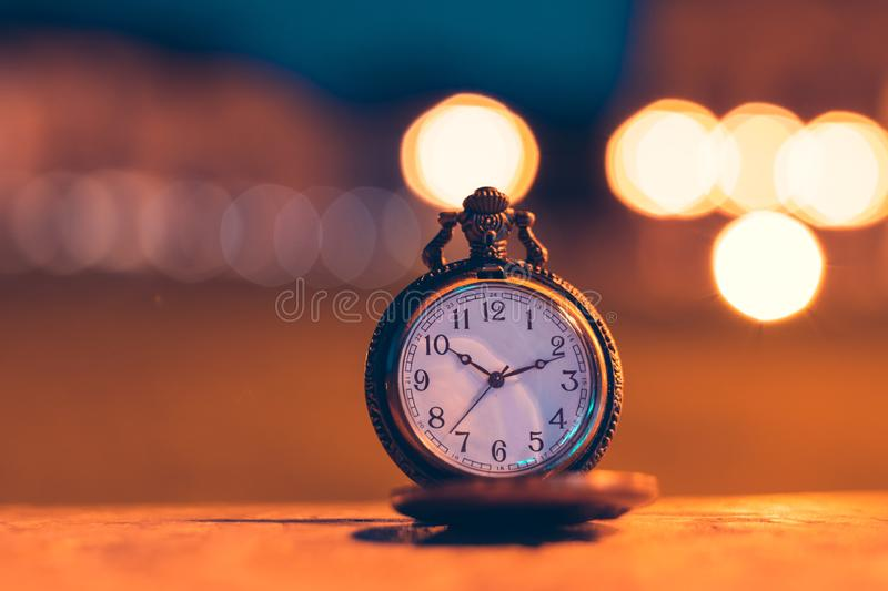 An old pocket watch photographed close to the blurred background. Watches, olds, times, clocks, pockets, antiques, chains, retros, backgrounds, minutes royalty free stock image