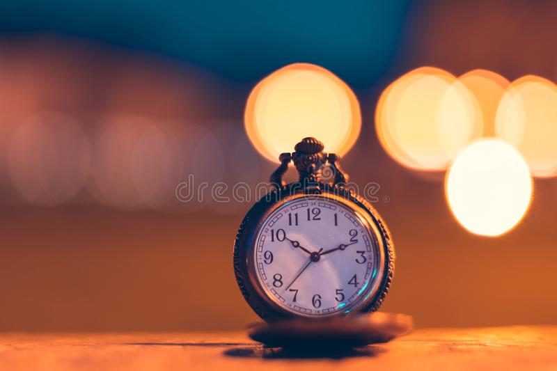 An old pocket watch photographed close to the blurred background. Watches, olds, times, clocks, pockets, antiques, chains, retros, backgrounds, minutes royalty free stock images