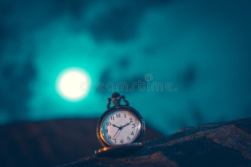 An old pocket watch photographed close to the blurred background. Watches, olds, times, clocks, pockets, antiques, chains, retros, backgrounds, minutes stock images