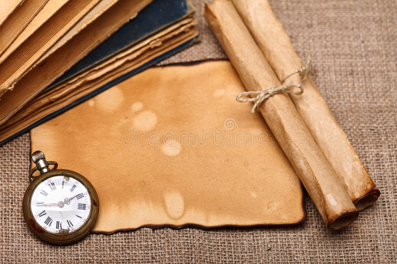 Old pocket watch with rolls and books royalty free stock images