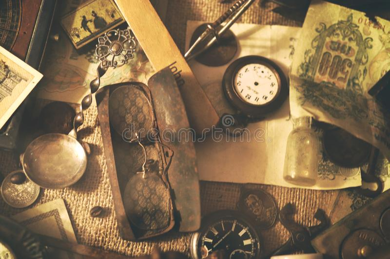 Old pocket watches, banknotes and coins of the Russian Empire, glasses in a case, silverware. Different antique items on the table: old pocket watches, banknotes royalty free stock images