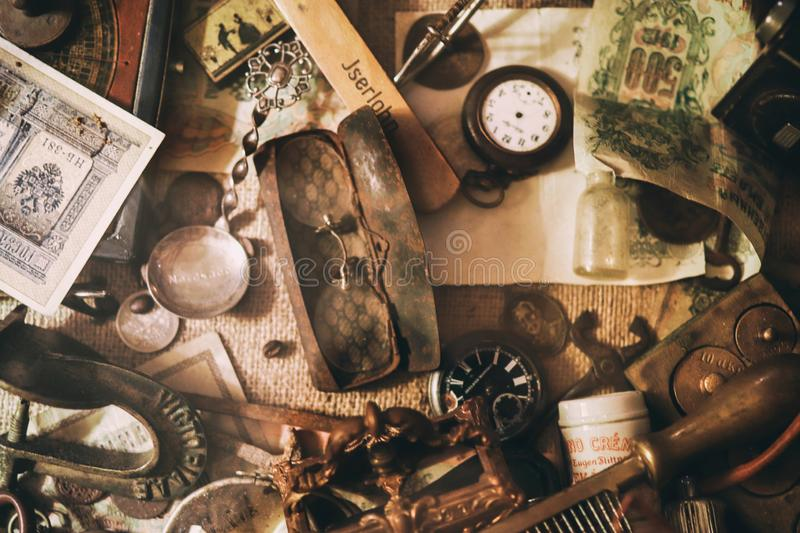 Old pocket watches, banknotes and coins of the Russian Empire, glasses in a case, silverware. Different antique items on the table: old pocket watches, banknotes royalty free stock photo