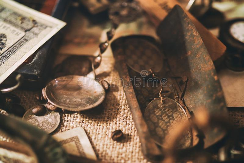 Old pocket watches, banknotes and coins of the Russian Empire, glasses in a case, silverware. Different antique items on the table: old pocket watches, banknotes stock images