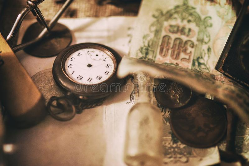 Old pocket watches, banknotes and coins of the Russian Empire, glasses in a case, silverware. Different antique items on the table: old pocket watches, banknotes stock photos