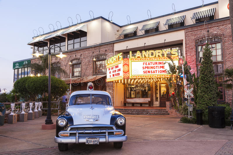 Old Police Car in Kemah Boardwalk, Texas. KEMAH, TX, USA - APR 14, 2016: 1952 Chevrolet Styleline Deluxe historic police car and Landry's seafood restaurant at stock photography
