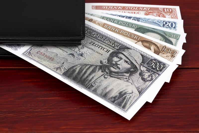 Old Polish money in the black wallet. On a wooden background stock photos