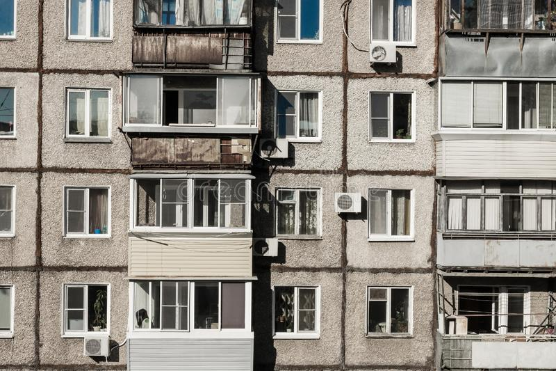 Old, poor, cheap housing. The wall of a dilapidated apartment building, windows and old balconies. A terrible condition of housing, bad conditions, cheap royalty free stock photos