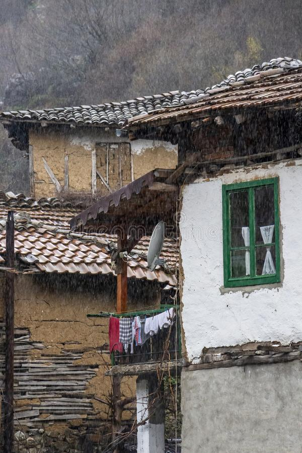 Old poor houses under the rain in the village of Pirin in Pirin Mountains, Bulgaria, architectural detail stock image