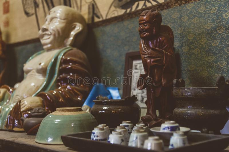 Old porcelain Buddha figure in antique shop in China stock images