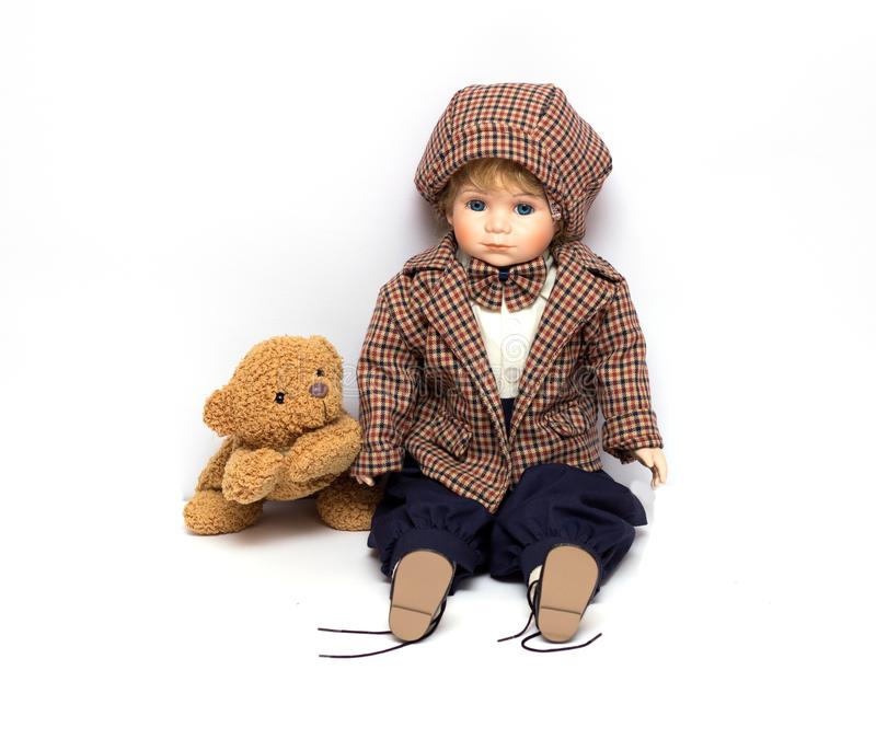 Old porcelain doll on White Background, ceramic dolls and a teddy bear. royalty free stock image