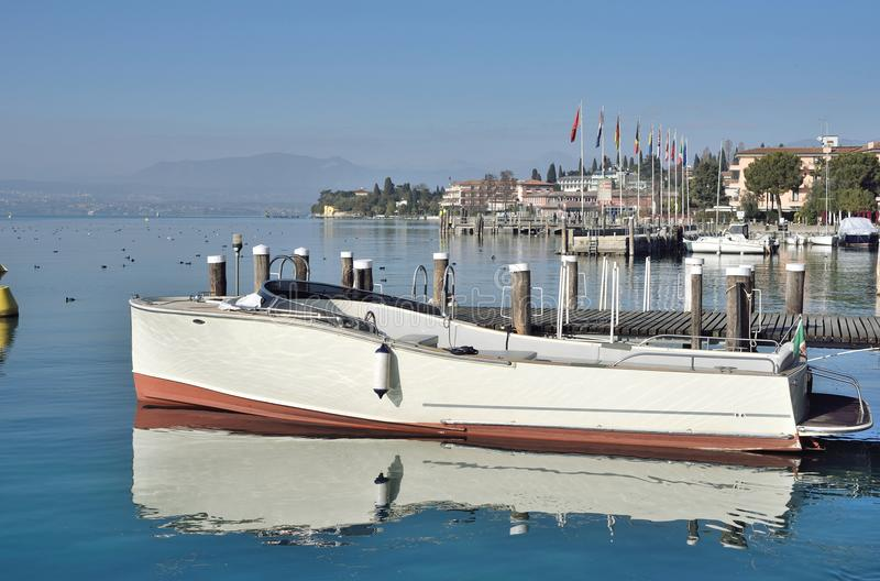 Old powerboat on Garda Lake. Old powerboat moored on calm waters of Garda lake, Sirmione, in Italy stock photography
