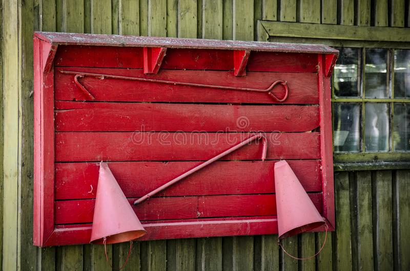 Old protective shield with a tool for firemen. Fire shield, hanging on an wooden surface royalty free stock photos