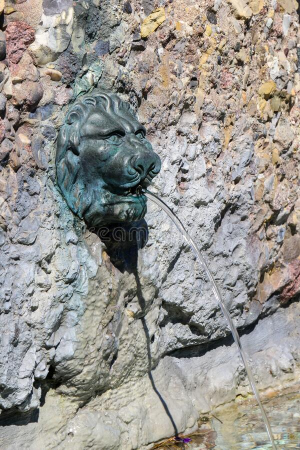 Old public fountain with a bronze lion head stock photography