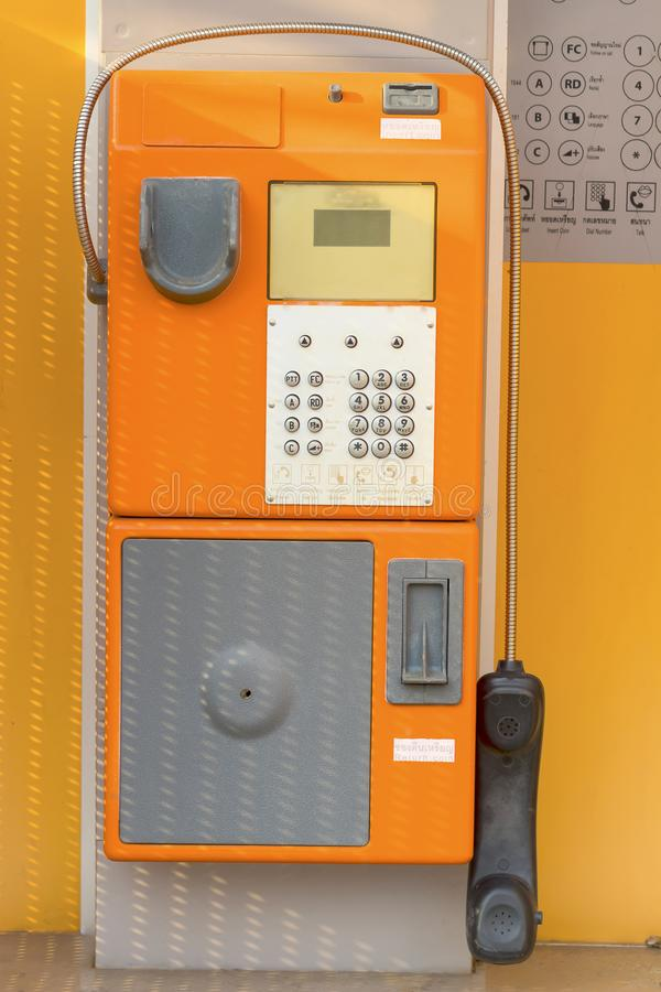 Old public phone booth orange color for coins royalty free stock image
