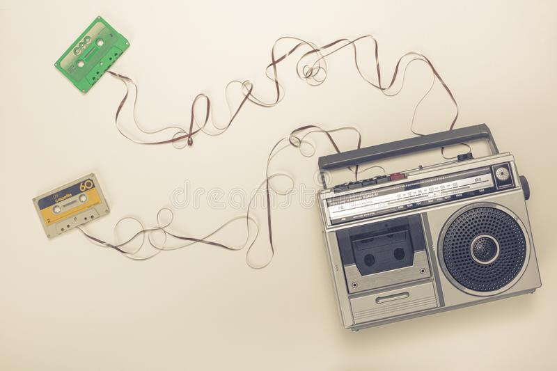 Old radio with tape recorder and cassettes with ribbon forming a wire. Flat lay style royalty free stock image