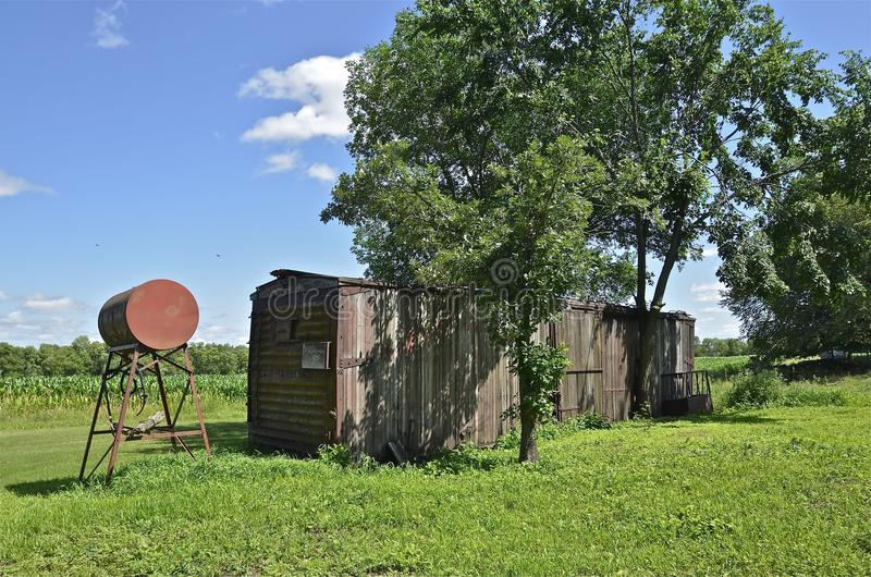 Old railroad boxcar on farm. An old railroad boxcar converted into farm storage stand alongside a corn field stock photos