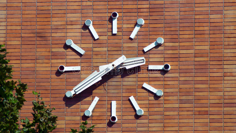 Old railway clock on the brick wall. Picture of unkempt old railway clock on the brick wall, taken at a shiny day. Parts of the clock are breaking up, only the royalty free stock image