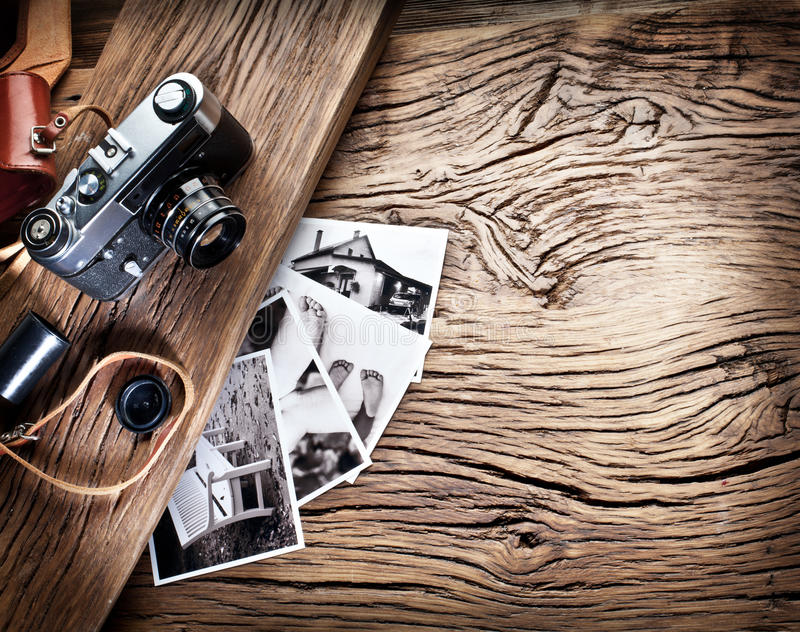 Old rangefinder camera and black-and-white photos. Old rangefinder camera and black-and-white photos on the old wooden table stock photos