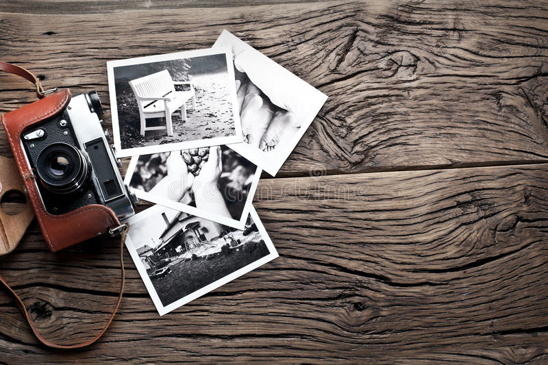 Old rangefinder camera and black-and-white photos. Old rangefinder camera and black-and-white photos on the old wooden table stock images