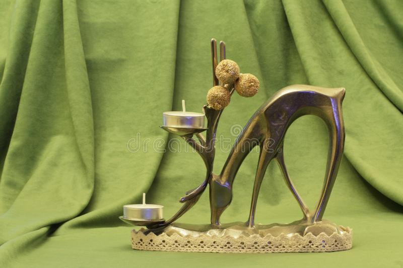 Old rare metal statuette of deer in the form of candlestick with wax candles and decorative golden apples on green fabric. Background stock image