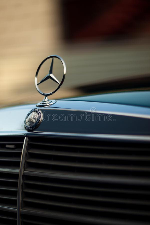 Old rare vintage green Mercedes-Benz hood, badge, radiator grille on blurred background. Editorial use only. The symbol of rich life stock photography