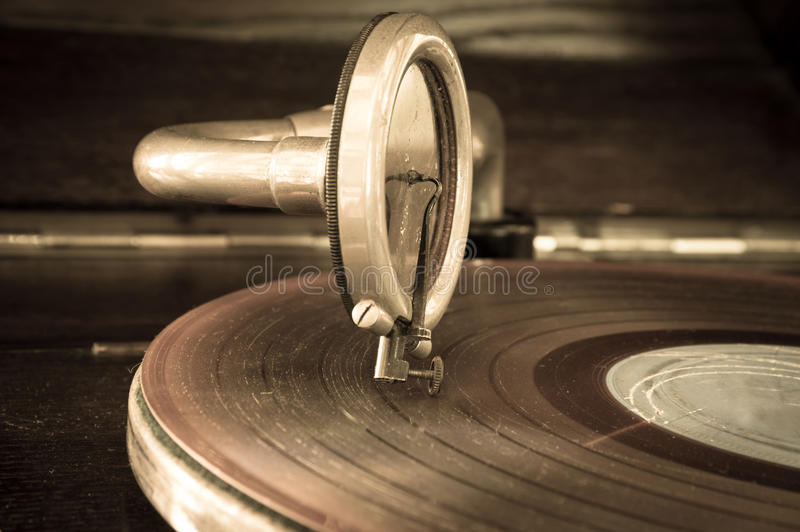 Old record player stylus on a rotating disc. Vintage filtered royalty free stock photo
